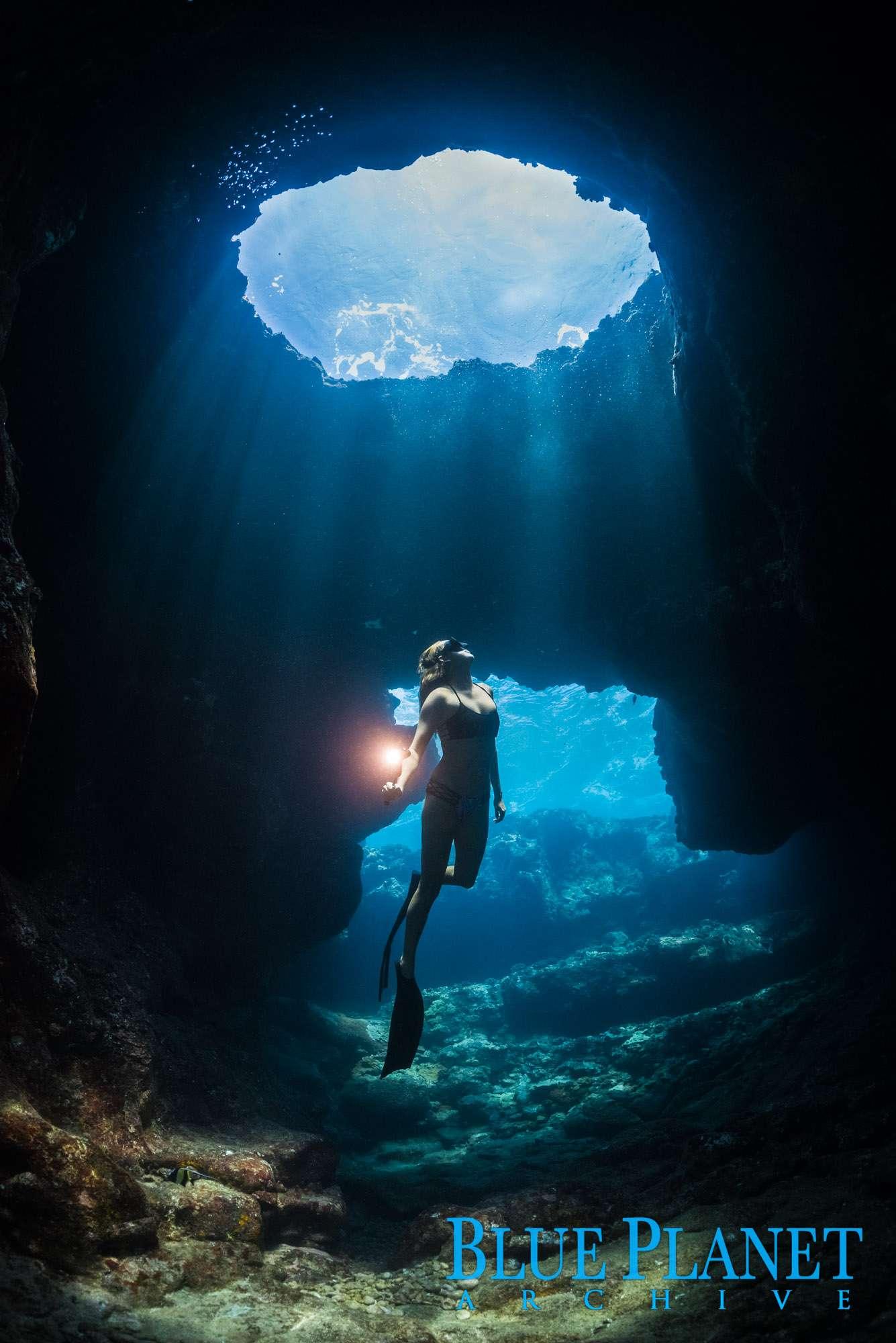 Free Diver Exploring Underwater Lava Tube